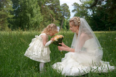 mother in her wedding dress holding a wedding bouquet with little daughter in wedding dresses. Outdoors summer portrait royalty free stock photos