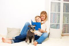 Mother with her 10 years old kid girl reading the book, casual lifestyle photo series. Cozy homely scene royalty free stock photo