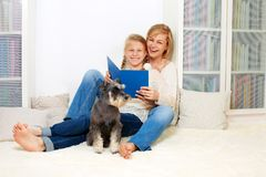 Mother with her 10 years old kid girl reading the book, casual lifestyle photo series. Cozy homely scene stock image