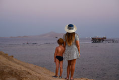 Mother with her young son on a sunset beach Stock Images