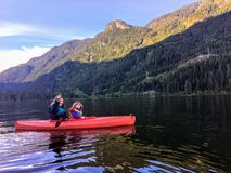 A mother and her young 5 year old girl kayaking together on the beautiful calm ocean water of Indian arm. stock photos