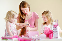 Mother and het two daughters wrapping a gift Royalty Free Stock Photos
