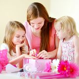 Mother and het two daughters wrapping a gift Royalty Free Stock Photo