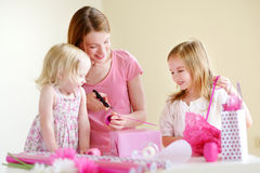 Mother and het two daughters wrapping a gift Stock Image