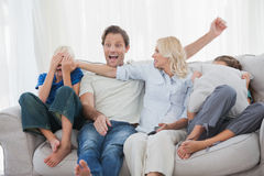 Mother hiding the face of her son while watching a horror movie Stock Photos