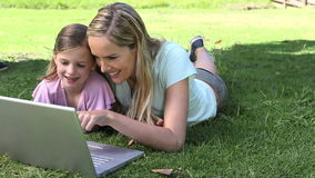 Mother and his daughter using a laptop in a park. Video of a mother and his daughter using a laptop in a park stock video