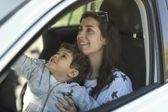 Mother with his little son inside a car. Parking and smiling at mirror stock photo
