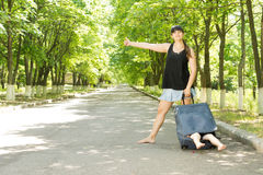 Mother hitchhiking with her son in a suitcase. Fun image of a pretty barefoot young mother hitchhiking on a rural leafy avenue with her son in a suitcase with Royalty Free Stock Photo