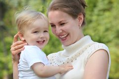 Mother hold baby on hands outdoor in summer Stock Photos