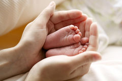 Mother hold feets of newborn child Stock Photos