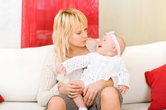 Mother hold her baby girl at home Stock Photo