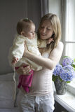 Mother hold her blond serious baby girl Royalty Free Stock Image