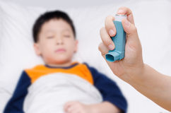 Mother holding asthma inhaler. Foreground and sick little boy in background Stock Images
