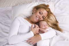 Mother holding baby boy asleep in her arms Royalty Free Stock Image