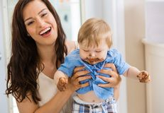 Mother Holding Baby Boy With Cake Icing On Face Stock Photos