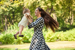 Mother holding baby girl on hands and spinning around at park Stock Images
