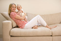 Mother holding baby girl (9-12 months), sitting on sofa, smiling, portrait Stock Image