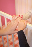 Mother holding baby hand and daughter hand Royalty Free Stock Images