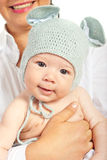 Mother holding baby with knitted cap Stock Photo