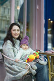Mother Holding Baby On Lap Sitting In Outdoor Cafe. Portrait of happy young mother holding baby on lap sitting in outdoor cafe stock images