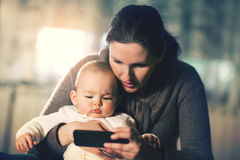 Mother holding baby and looking at smart phone Stock Photography