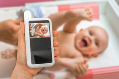 Mother is holding baby monitor camera for safety of her baby. Hand of mother is holding baby monitor camera for safety of her cute baby Royalty Free Stock Photos