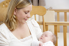 Mother Holding Baby In Nursery royalty free stock photography