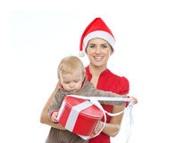 Mother  holding baby opening Christmas present Stock Images