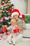 Mother holding baby opening Christmas present box Stock Photos