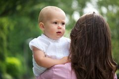 Mother holding baby over shoulder outdoors Stock Photography