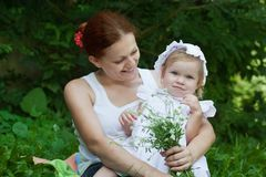 Mother holding a baby in a park Stock Photography