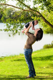 Mother holding baby in park. Young mother holding her baby daughter in an outdoor park by a river Royalty Free Stock Image