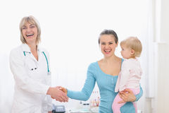 Mother holding baby and shaking hand to doctor Royalty Free Stock Photo