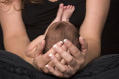 Mother holding baby. Small newborn baby with its head supported by its mother's hands Royalty Free Stock Image