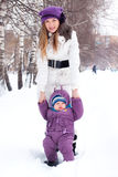 Mother holding a baby, snow, winter park. Walk Royalty Free Stock Photos