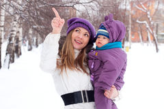 Mother holding a baby, snow, winter park Stock Photo