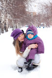 Mother holding a baby, snow, winter park, walk Stock Images