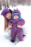 Mother holding a baby, snow, winter park, walk Royalty Free Stock Photography