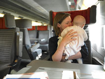 Mother Holding Baby on Train stock images