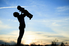 Mother holding baby up in the back lit Royalty Free Stock Image