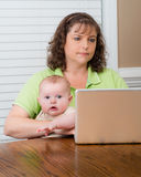 Mother holding baby while working on computer Royalty Free Stock Photo