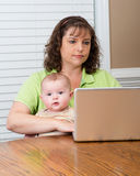 Mother holding baby while working on computer Stock Photo