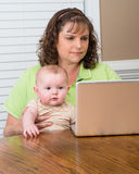Mother holding baby while working on computer Stock Photography