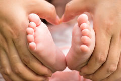 Mother holding the feet of the baby Royalty Free Stock Photo
