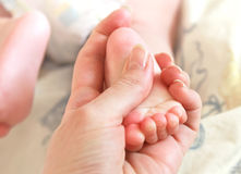 Mother holding beautiful baby foot Stock Photography