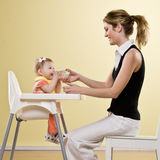 Mother holding bottle for baby in highchair Stock Photography