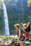 Mother holding child in backpack explore rainforest waterfall Stock Photos