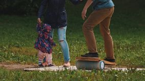 Mother holding child hand as father attempts to balance on a board on cylinder stock footage