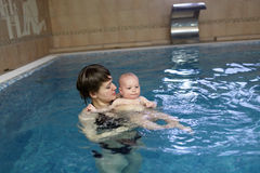 Mother holding child in pool. Mother is holding her child in an indoor swimming pool Stock Photography