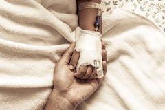 Mother holding child's hand who have IV solution in the hospital Royalty Free Stock Photo